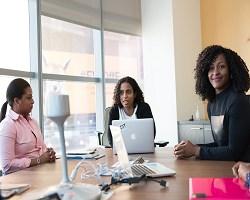 Group of black women in boardroom talking