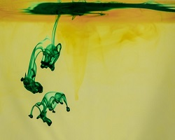 Creative visual, yellow liquid with green paint seeping in
