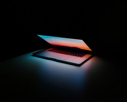 Laptop with faint glowing screen in dark room