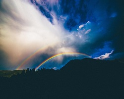 Rainbow in clouds and mountains