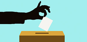 hand in shadow over a ballot box