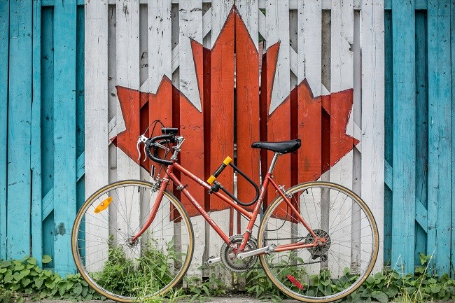 Cycle leaning against a fence with a Canadian Flag