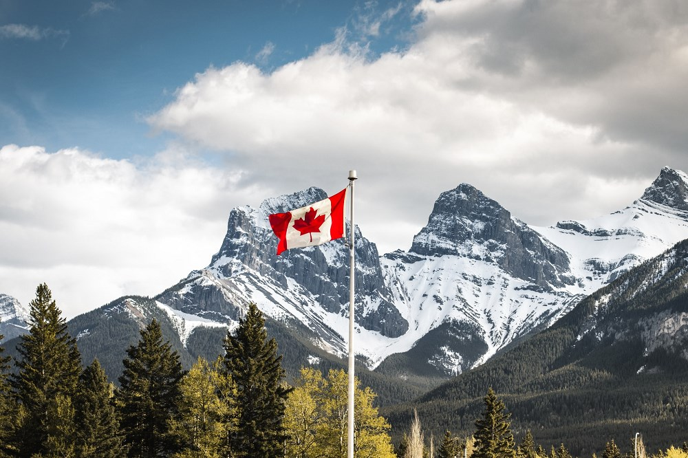 Canadian flag in front of mountains