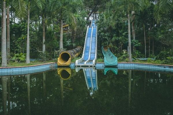 A dirty, old slide ending in dank water