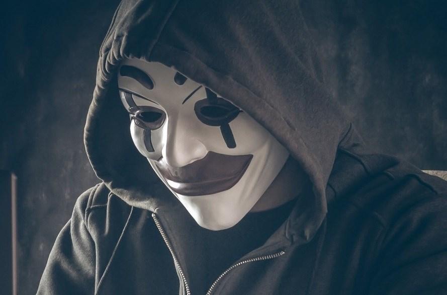 Computer hacker wearing clown mask