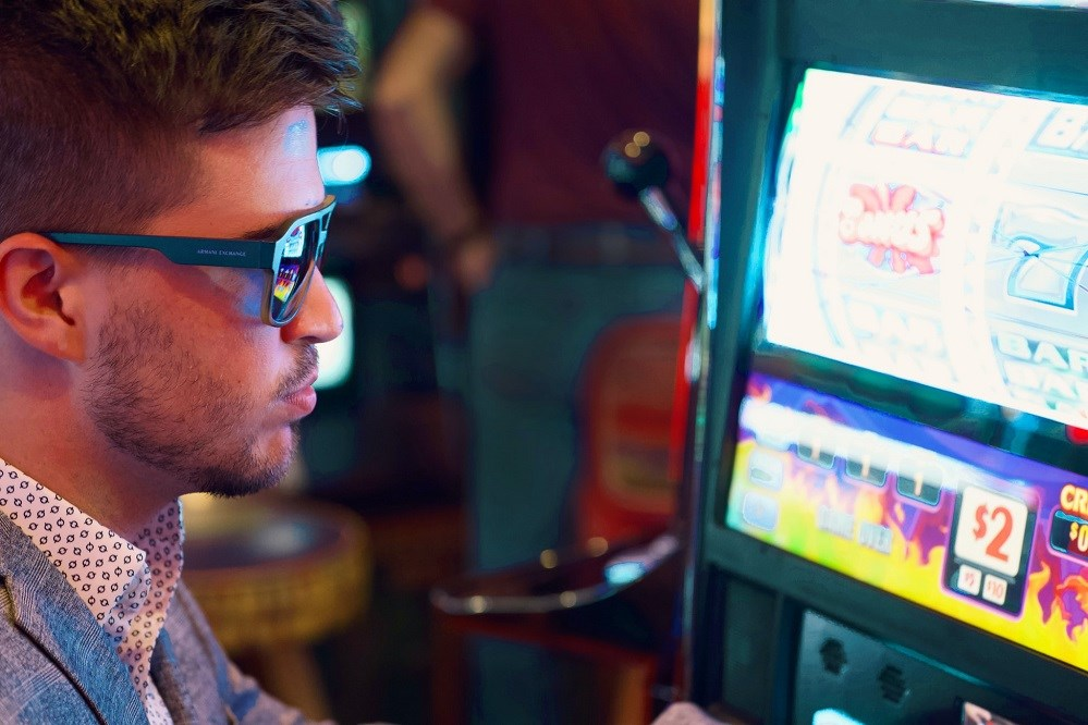 Guy in sunglasses at a slot machine