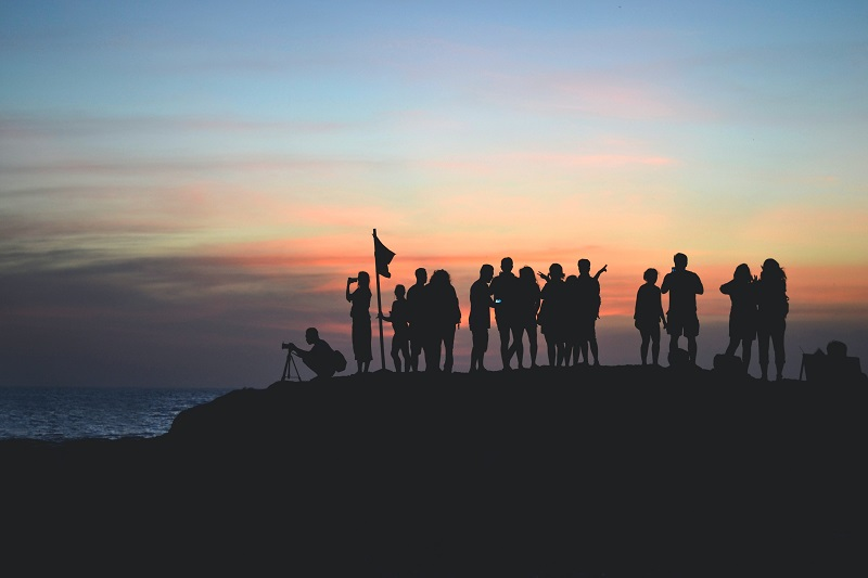 Group on summit in front of a sunrise