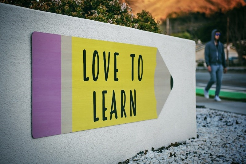 "Pencil-shaped sign that says ""Love to Learn"""