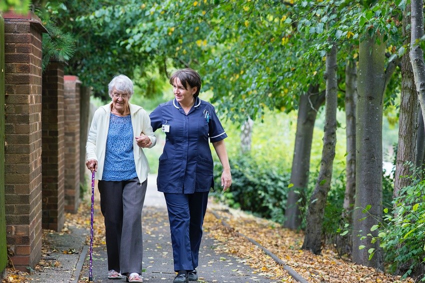 woman walking with carer