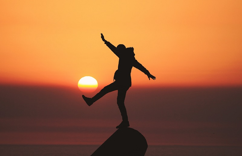 Person balancing on rock in sunset