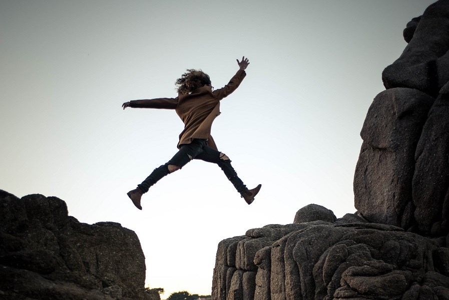 Person Jumping Between Rocks