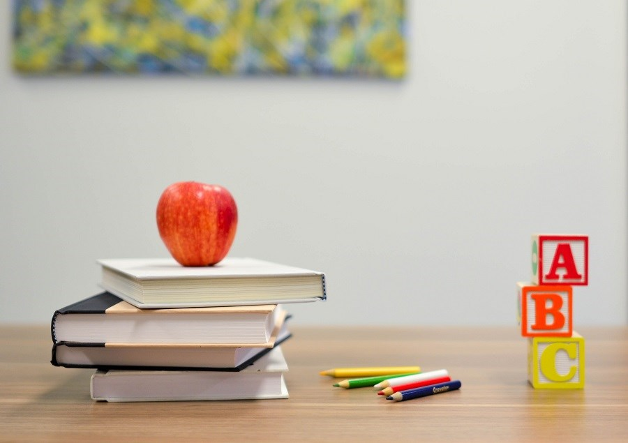 Classroom with books and apple on desk