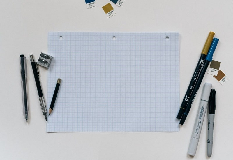 Sheet of paper seen from above, with pencils to the right and left of the paper.