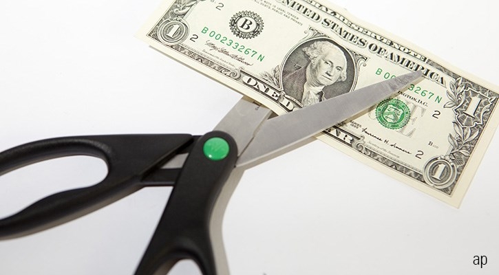 Scissors cutting U.S. dollar bill