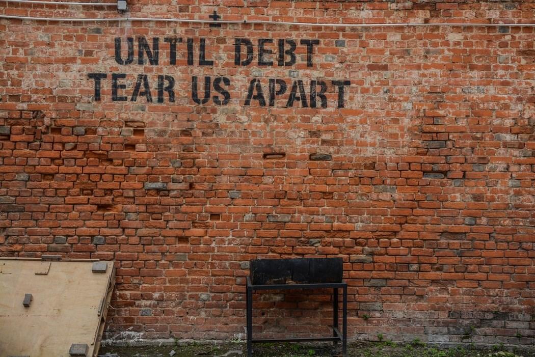 "Graffiti on wall that says ""Until debt tears us apart"""