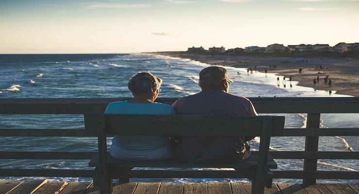 to personer sitter på en benk og ser utover stranden og havet.