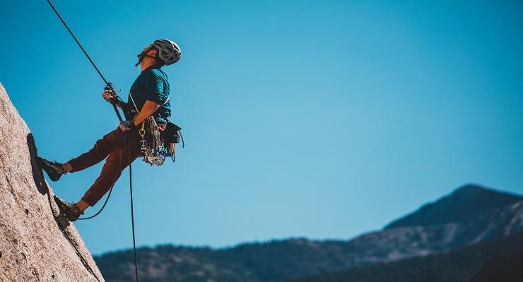 Mann som klatrer i fjellet