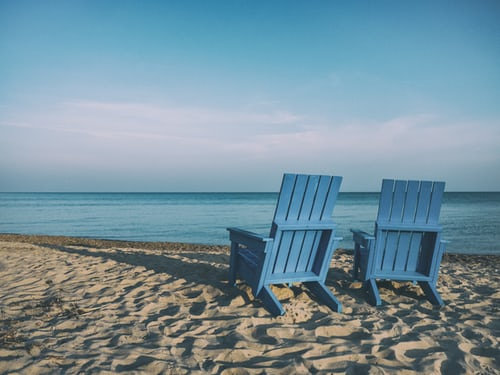 Two cottage chairs on a beach
