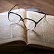 Brille liegt auf aufgeklapptem Buch